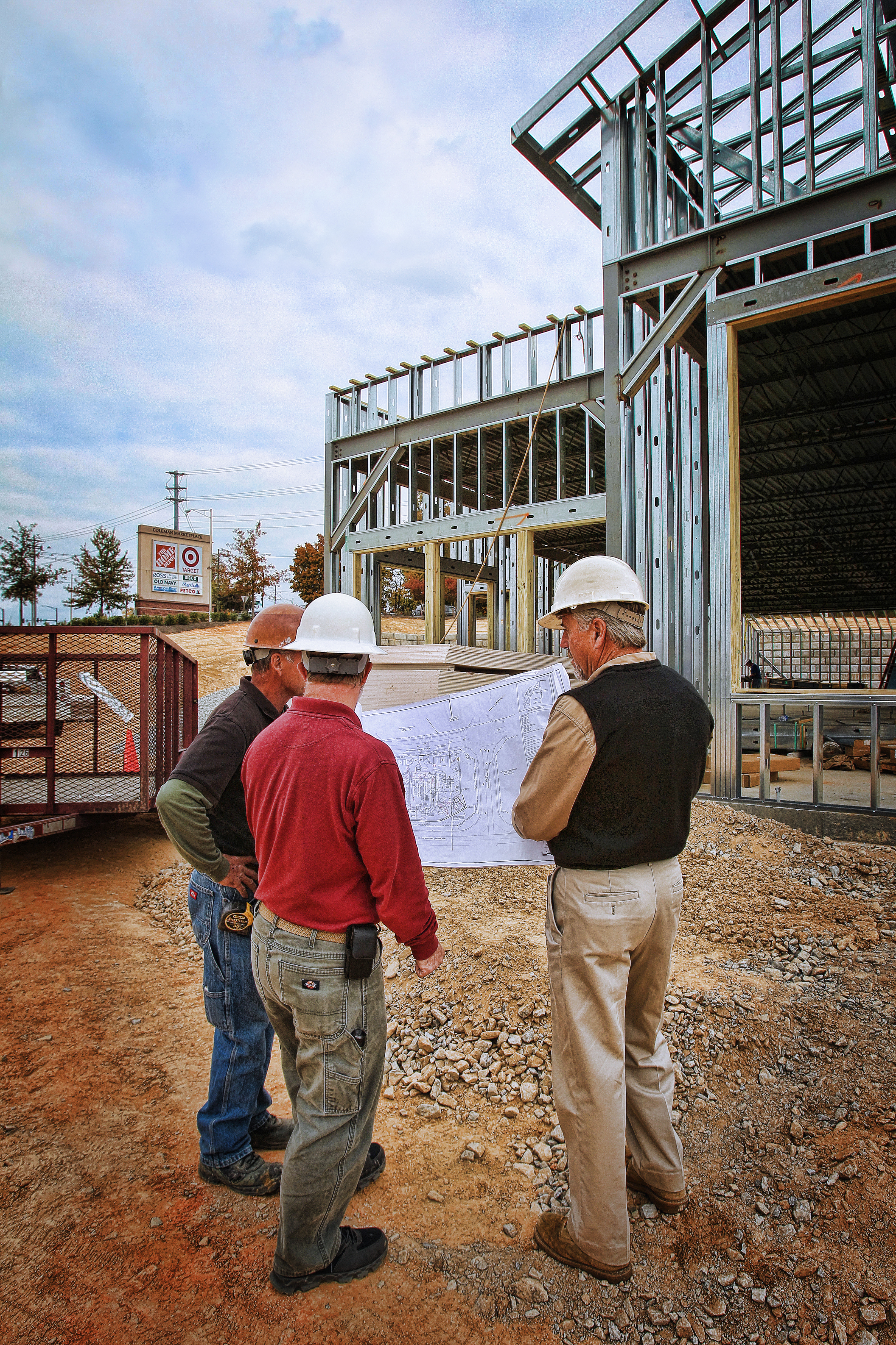 Three Men Examining Building Plans near a Construction Site